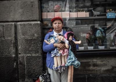 Elsa Silva, vendedora ambulante, ofrece al público sus muñecas, mientras pasa, frente a ella, la marcha de las y los trabajadores
