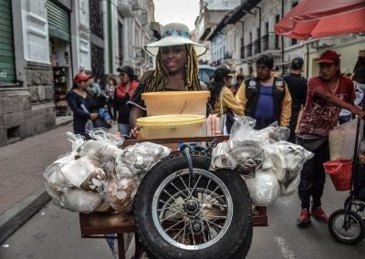 Katy Mendez, vendedora de jugos, camina con su carrito mientras avanza la marcha del 1ero de Mayo